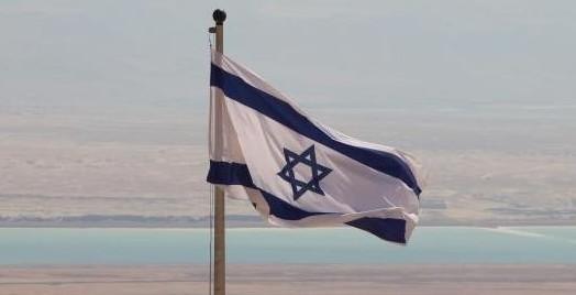 Israels flagg vaier i vinden på Masada. Dødehavet og nasjonen Jordan i bakgrunn.